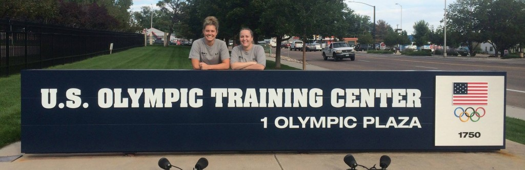 "Kelsey Bocken and Callie Martin are standing behind a sign that reads, ""U.S. Olympic Training Center."